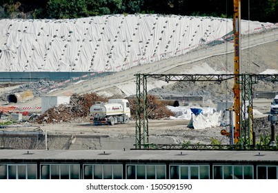 GENOA, ITALY - SEPTEMBER 14, 2019: work machines and in the reconstruction site of the new bridge for Genoa. A tank truck wets the yard's ground to break down the dust.