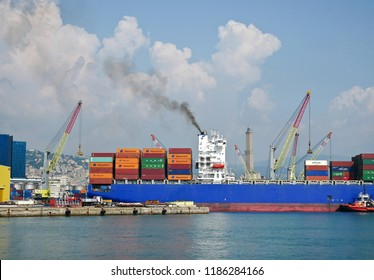 GENOA, ITALY - SEPTEMBER 19, 2018: container ship in maneuver in the port. Black smoke from the smokestack.
