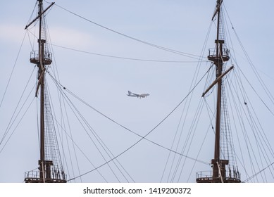 Genoa, Liguria / Italy - 08 July 2018: A Vueling airlines aircraft over Genova between two masts of the ship.