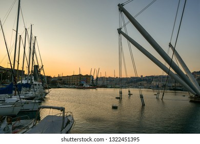 Genoa, Liguria / Italy - February 10 2018: Scenic view of the Old Port (Porto Antico) with docked boats and the famous architectural structure Bigo at sunset