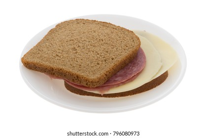 A genoa salami and provolone cheese on stone ground wheat bread sandwich on a plate isolated on a white background.