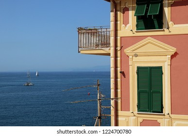 Genoa, - View of blue Tigullio gulf from the rocky cape closing Boccadasse bay and the profile of a characheristic Ligurian painted house
