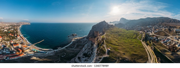 Genoese fortress in Sudak, Crimea. Aerial panorama view of ruins of ancient historic castle on crest of mountain near sea and small town at foot of rocks. Beautiful summer tourist landscape