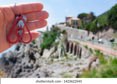 Genova, Italy. May, 2019. Woman holds the key with the logo of a popular company Airbnb.Travel around the world with Airbnb. Logo and the city on the background. Home concept.