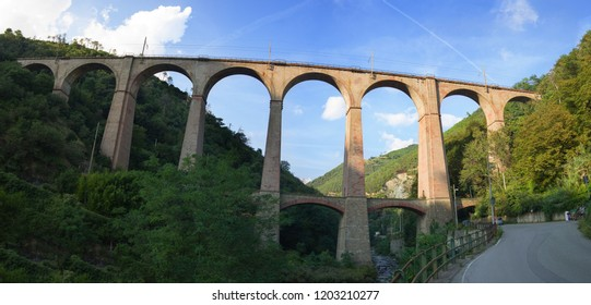 Genova Italy_September 15, 2018: old arched railway bridge made with solid brick   in a gorge between two hills