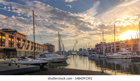 Genova, Liguria, Italy - August 2019: Beautiful sunset view of old harbor (Porto Antico), sailboats docked at quay nearby aquarium, reflections on water, sun setting