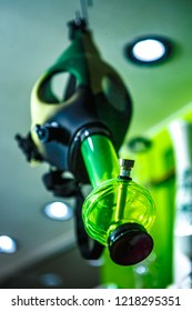 GENOVA,ITALY-12 OCTOBER,2018: Ganja shop sell legalized marijuana, glass bong pipes and accessories for smoking weed.Legal light drug store in close up. Gas mask with hookah in green light