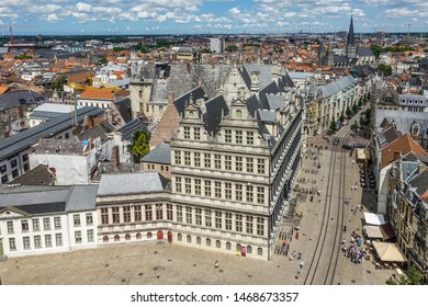 Gent, Flanders, Belgium -  June 21, 2019: Shot from top Belfry. Historic city or town hall in middle of cityscape of buildings and roofs stretching to flat horizon. Blue cloudscape.