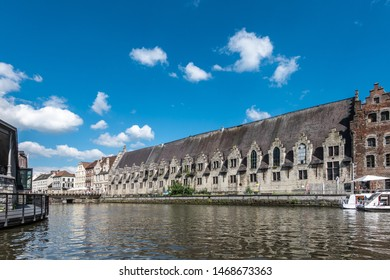 Gent, Flanders, Belgium -  June 21, 2019: Historic gray-stone long facade of Vleeshuis, medieval meat trading floor, along Leie River under blue sky with white clouds..