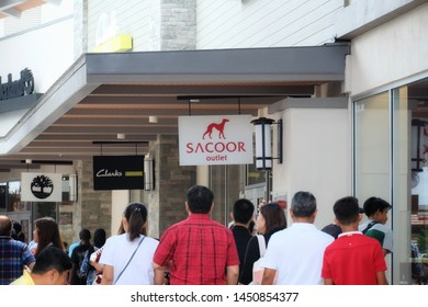 """""""Genting, Malaysia- Circa July, 2019: A selective focus picture of Sacoor Brother Outlet during weekend with bigger crowd. Sacoor Brothers is a Portuguese luxury clothing retail company."""""""