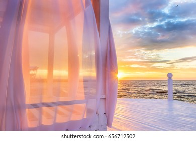 A gentle beautiful early morning by the sea. White porch with verandah. A gazebo with aerial wind-blown pink curtains on the seashore at dawn. Rays of the sun making their way through the fabric.