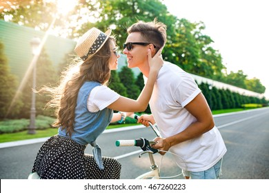 Gentle couple in love on road on sunset. Pretty girl with long curly hair sits on bike, handsome guy in front is going to kiss her.