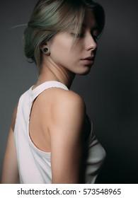 Gentle cute young woman. Studio portrait.
