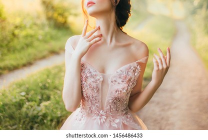 gentle elegant photo of girl with fair skin and dark hair, cute slender lady with bare shoulders twisted off straps of pink peach shiny dress, princess touches long neck with slender fingers, no face