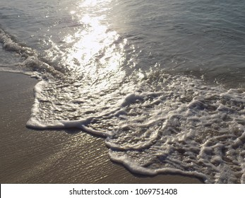 Gentle Foaming Waves lap a Sunlit Beach.