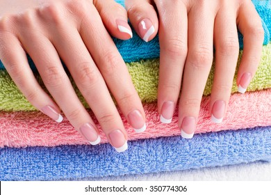 Gentle french manicure on bright towel. Nail salon.