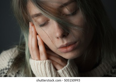 Gentle girl with wool sweater and hair on face. Eyes closed