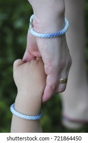 gentle hands of mother and daughter in identical beaded bracelets on a green background