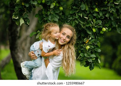 Gentle and happy young mother with blond hair holds her laughing little daughter on the background of an apple tree while walking in the park. Summertime. Childhood. Summer. Happy family. Lifestyle