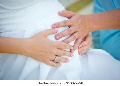 The gentle loving hands of future father and future mother on a stomach of the pregnant woman.