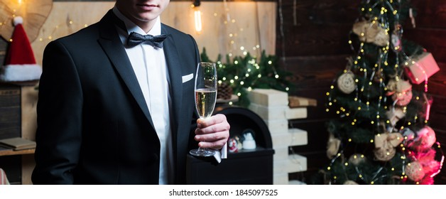 Gentle man wearing costume with bow and holding a glass of widow champagne at luxury new year decorated background. Christmas eve. Bright New Year's interior. Winter holidays