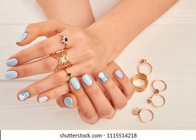 Gentle manicure and golden rings. Young woman hands with blue manicure wearing many golden rings. Woman beauty and jewelry.