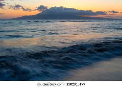 The gentle Maui surf reflects the last remaining orange sun light as the sun sets behind the island of Lanai, Hawaii.