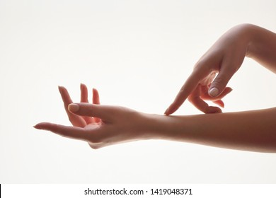 Gentle motion and gesture female hands. Be gentle to yourself metaphor. Close up of young woman softly touching her hands on white background. Elegant and graceful hands with slender graceful fingers.