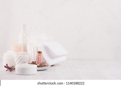 Gentle pink cosmetics oil, small flowers and white soap, cream, clay, towel on white wooden shelf, copy space, vertical.
