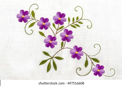 Gentle purple flowers with leaves embroidered satin stitch on white cloth