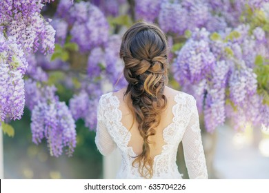 Gentle refined woman in the garden of beautiful wisteria trees.