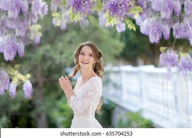 Gentle refined woman in the garden of beautiful wisteria trees.