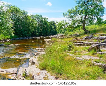 The gentle River Ribble splashes over rocks and boulders on a summer day in the Yorkshire Dales