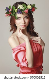 Gentle romantic appearance of the girl with a wreath of roses on her head and a pink dress.