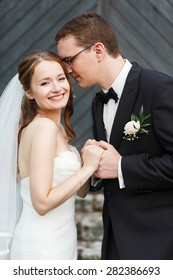 gentle stylish sgroom and bride holding hands and smiling on the background old door