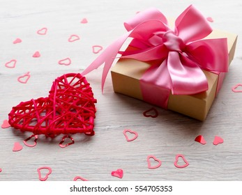 gentle sweet composition for Valentine's day, birthday, wedding in pink and red colors, little red heart box gift with pink bow, top view.