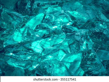 Gentle teal fond of sparkling water-washed grained rock with jagged edges, mysteriously lit cerulean celeste cyan glow. Closeup view with space for text