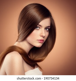 Gentle teenage girl showing her healthy long straight hair. Beautiful Caucasian female model with perfect glossy hair posing in studio.