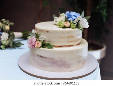 A gentle two-tier biscuit cake for a wedding with blue and pink flowers.