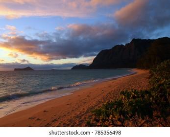 Gentle wave lap on Waimanalo Beach looking towards Rabbit island and Rock island  at dawn Oahu, Hawaii.  August 2014.