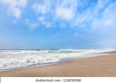 Gentle waves break on a sandy beach under a cloudy blue summer sky along California's Point Reyes National Seashore.