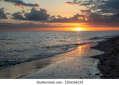 Gentle waves roll over a sandy beach at sunset on Sanibel Island, Florida.