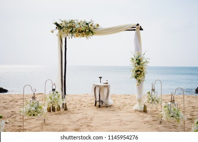 A gentle wedding arch on the sandy shore of the Ocean. Wedding ceremony in a tropical style.