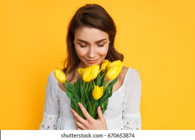 Gentle woman holding and smelling bunch of yellow tulips on yellow background.
