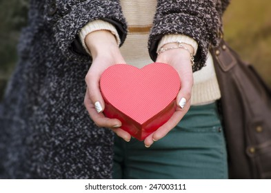 Gentle woman's hands holding a heart shaped box, shot outdoors