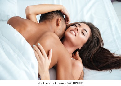 Gentle young couple lying and making love in bed at home