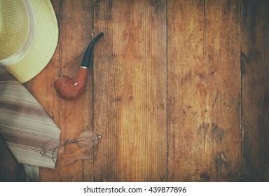Gentleman accessories on wooden background. top view. vintage filtered image