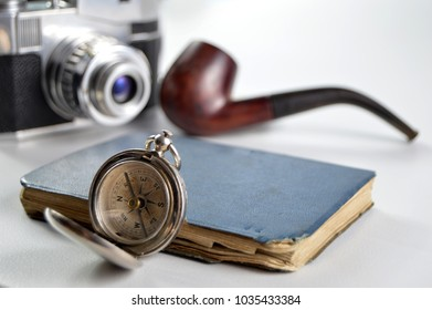 Gentleman adventurer concept with camera, pipe, compass and notebook on an isolated white background.