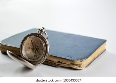 Gentleman adventurer concept with compass and notebook on an isolated white background.