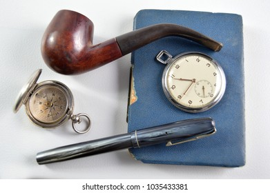 Gentleman adventurer concept with pipe, compass, pocket watch, pen and notebook on an isolated white background.